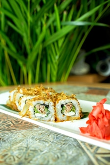 Vue latérale du rouleau de sushi de cuisine japonaise traditionnelle avec du thon servi avec du gingembre sur vert