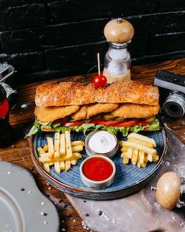 Vue latérale du sandwich avec des pépites de poulet salade de feuilles de cornichons et sauce servie avec des frites sur table en bois