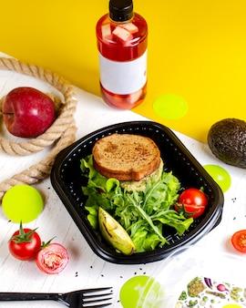 Vue latérale du sandwich végétalien avec avocat et tomates dans la boîte de livraison