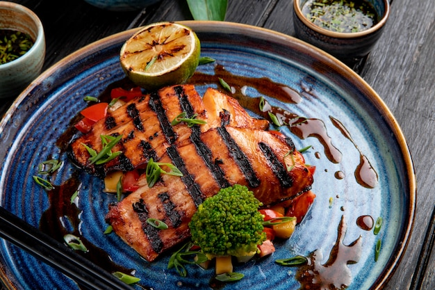 Vue latérale du saumon grillé aux légumes citron et sauce soja sur une assiette sur table en bois