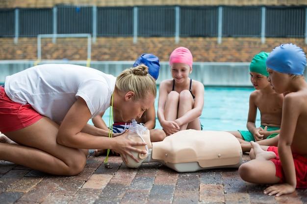 Vue latérale du sauveteur féminin démontrant les enfants au cours de la formation de sauvetage