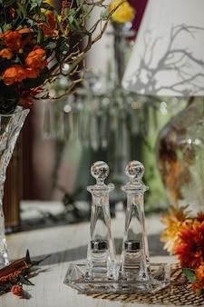 Vue latérale du sel et du poivre shaker en verre avec capuchon en métal sur la table