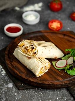 Vue latérale du shaurma kebab sur planche de bois avec des sauces sur fond noir