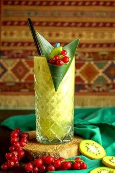 Vue latérale du smoothie kiwi en verre décoré de groseille fraîche