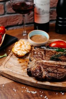 Vue latérale du steak de boeuf servi avec des légumes cuits au four et de la sauce barbecue sur planche de bois