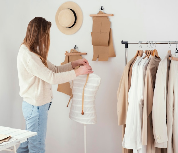 Vue latérale du tailleur féminin dans le studio avec des vêtements