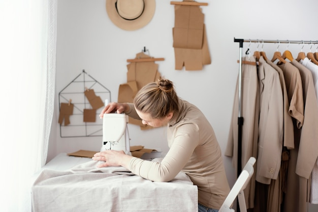 Vue latérale du tailleur féminin travaillant dans le studio avec machine à coudre