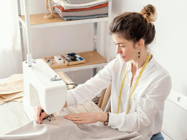 Vue latérale du tailleur féminin travaillant dans le studio