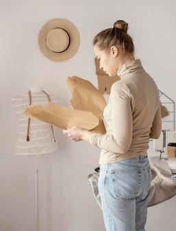 Vue latérale du tailleur féminin vérifiant les modèles dans le studio