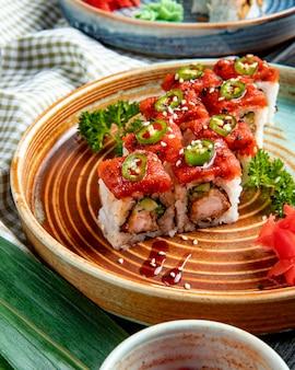 Vue latérale du tempura sushi maki aux crevettes et avocat sur une assiette