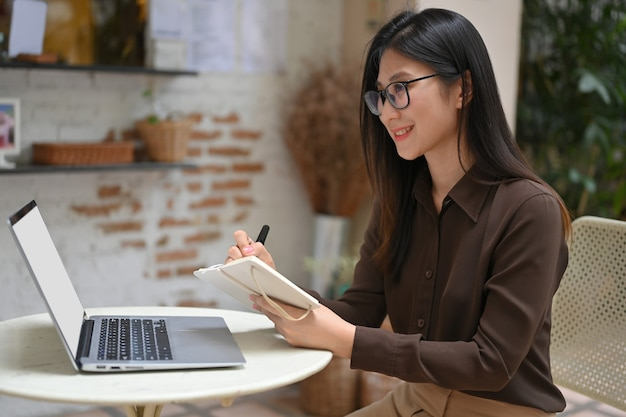 Vue latérale du travailleur féminin heureux d'écrire sur un ordinateur portable tout en travaillant avec un ordinateur portable au café