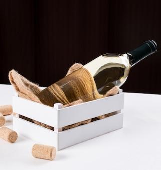 Vue latérale du vin blanc en bouteille dans une caisse en bois et un sac en lin sur une table blanche et une surface brune horizontale
