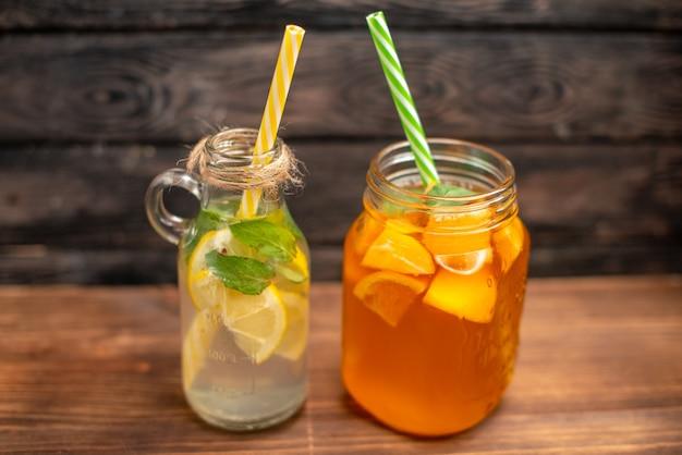 Vue latérale de l'eau de désintoxication fraîche et du jus de fruits servis avec des tubes sur fond marron