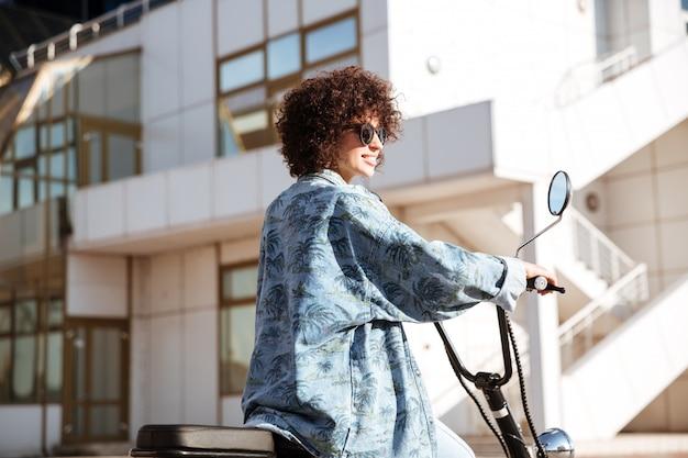 Vue latérale de l'élégante femme frisée en lunettes de soleil posant sur une moto moderne à l'extérieur