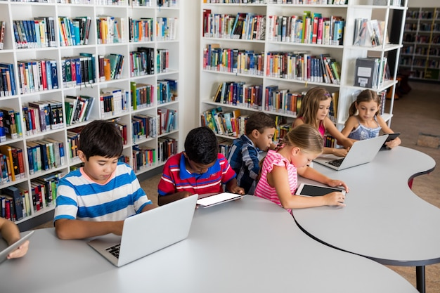 Vue latérale de l'élève à l'aide d'un ordinateur portable et d'une tablette pc