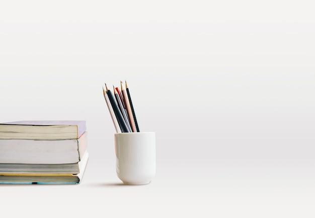 Vue latérale de l'empilement de livres et tasse de crayons, stylos sur le bureau avec espace de copie.