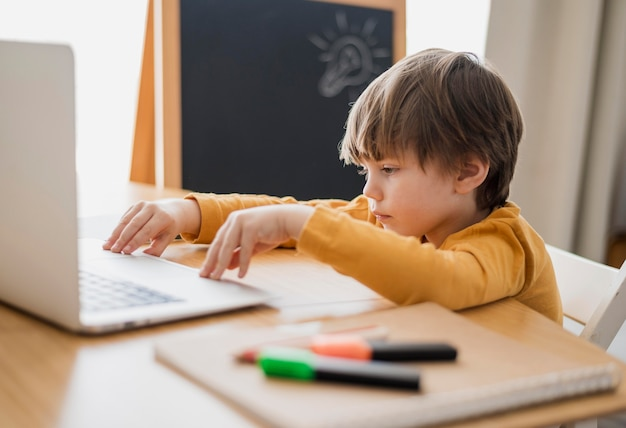 Vue latérale de l'enfant au bureau avec ordinateur portable et tableau noir