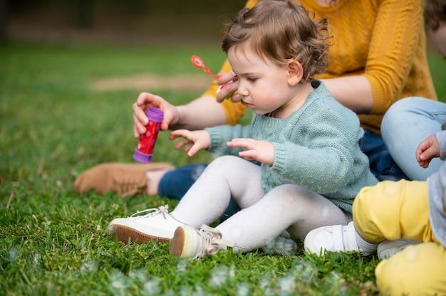 Vue latérale de l'enfant à l'extérieur dans le parc avec les mères lgbt