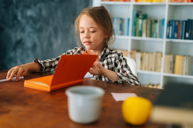 Vue latérale d'un enfant mignon d'école d'élève faisant ses devoirs en lisant un livre de papier assis à table dans la lumière