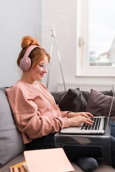 Vue latérale de l'enseignante à l'aide d'un ordinateur portable et d'un casque à domicile pour cours en ligne
