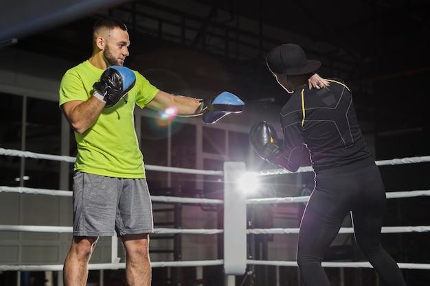 Vue latérale de l'entraîneur et du boxeur féminin dans le ring