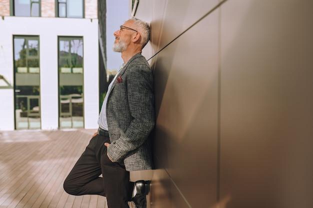 Vue latérale d'un entrepreneur réfléchi avec ses mains dans les poches appuyé contre le mur
