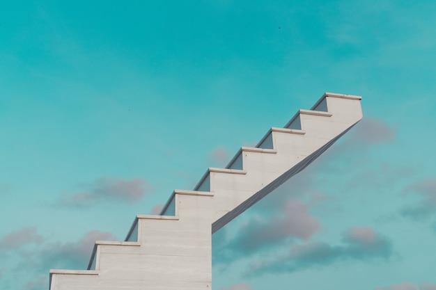 Vue latérale des escaliers en bois blanc avec ciel bleu fantastique et nuages, en arrière-plan, objectif, concept de réussite