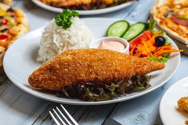 Vue latérale escalope de poulet croustillant panco poitrine de poulet avec garniture de riz concombre tomate carotte et sauce sur une plaque