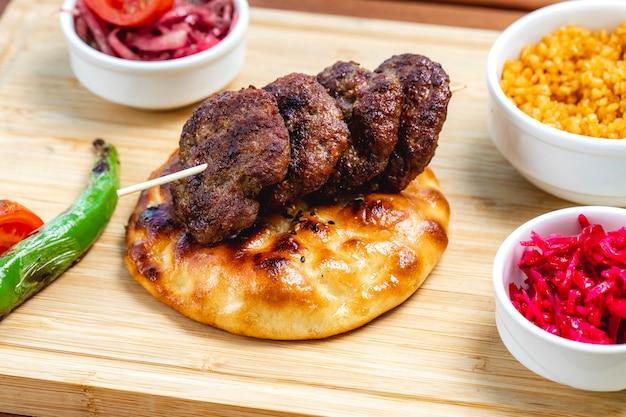 Vue latérale des escalopes de viande grillée sur du pain avec de la tomate au poivron vert et du chou mariné sur la table