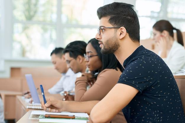 Vue latérale d'un étudiant arabe assis à l'université.