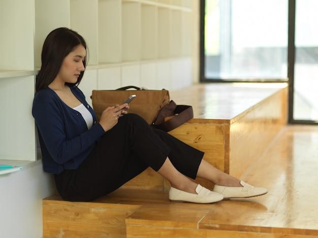 Vue latérale de l'étudiante à l'aide de smartphone tout en étant assis détendu dans l'espace de travail co
