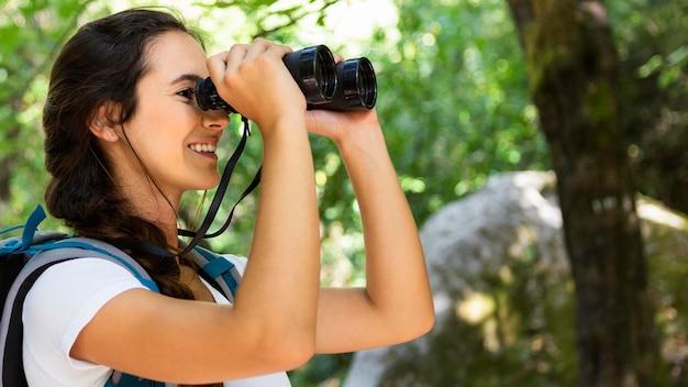 Vue latérale d'une femme admirant la nature à travers des jumelles