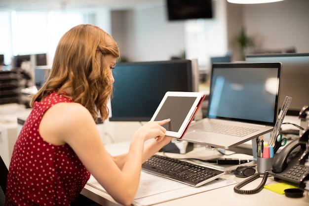 Vue latérale de la femme d'affaires à l'aide de tablette numérique au bureau