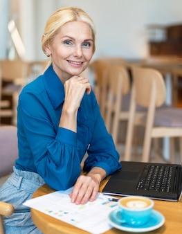 Vue latérale de la femme d'affaires aînée smiley posant tout en travaillant sur ordinateur portable et en prenant un café