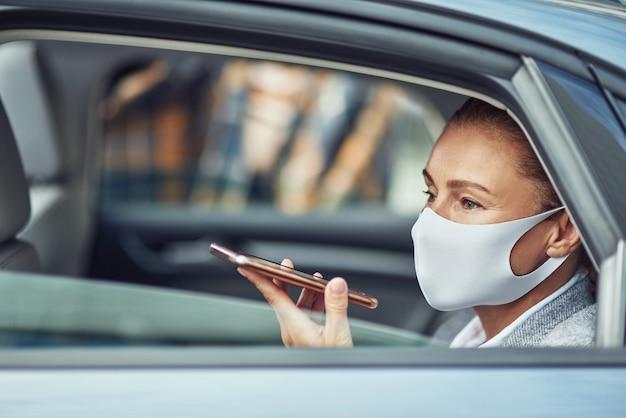Vue latérale d'une femme d'affaires caucasienne portant un masque de protection médicale parlant sur smartphone