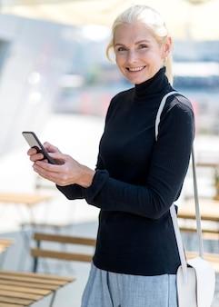 Vue latérale d'une femme d'affaires plus âgée smiley avec smartphone à l'extérieur