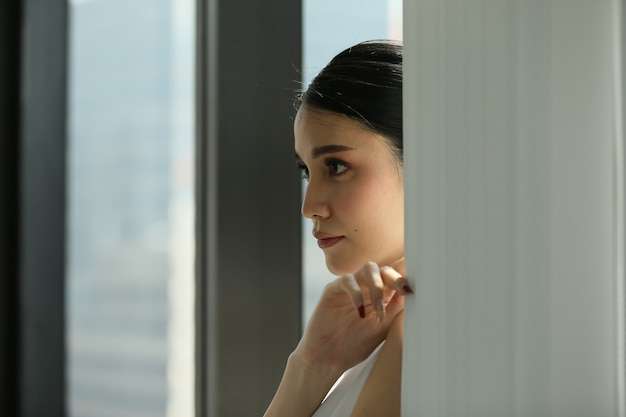 Vue latérale d'une femme d'affaires regardant par la fenêtre.