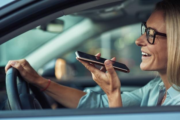 Vue latérale d'une femme d'affaires souriante utilisant un smartphone enregistrant un message vocal tout en conduisant une voiture
