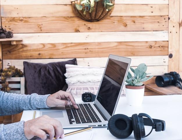 Vue latérale d'une femme âgée travaillant sur un ordinateur portable en plein air sur une table blanche. bureau extérieur alternatif. fond en bois. appareils et appareil photo à proximité d'elle