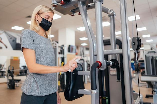 Vue latérale de la femme à l'aide de désinfectant sur l'équipement de gym