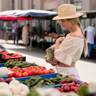 Vue latérale femme à l'aide de sac bio pour les légumes