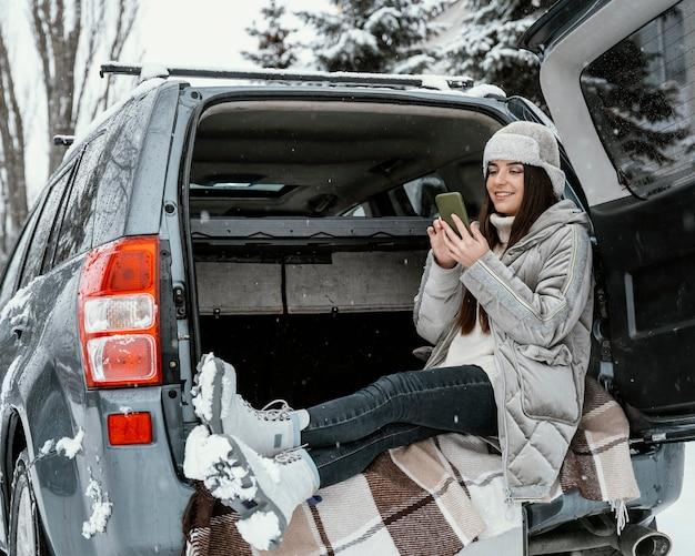 Vue latérale de la femme à l'aide de smartphone lors d'un voyage sur la route