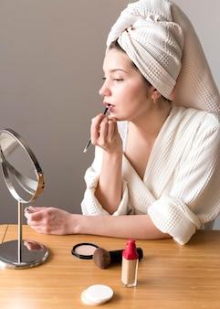 Vue latérale femme appliquer le rouge à lèvres
