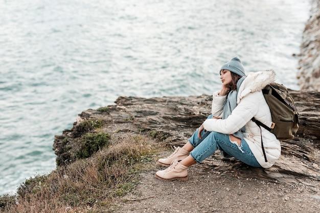 Vue latérale d'une femme appréciant la vue sur la plage seule