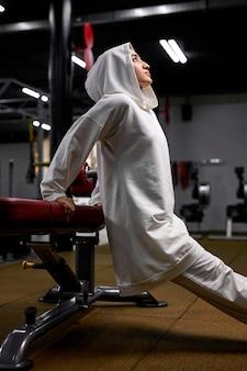 Vue latérale sur une femme arabe ayant un entraînement intense, s'appuie sur des équipements sportifs, soulevant le corps et s'accroupissant. femme musulmane en hijab faire de l'exercice seul