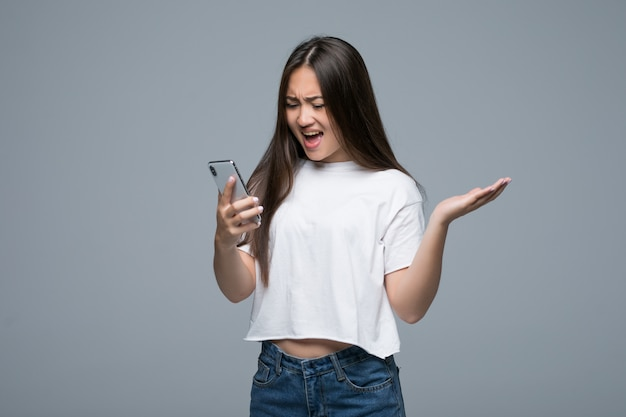 Vue latérale d'une femme asiatique tenant un smartphone et regardant en arrière sur fond gris