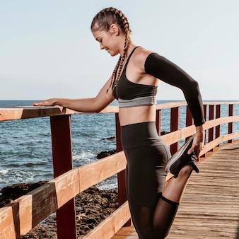 Vue latérale d'une femme athlétique qui s'étend à l'extérieur au bord de la plage