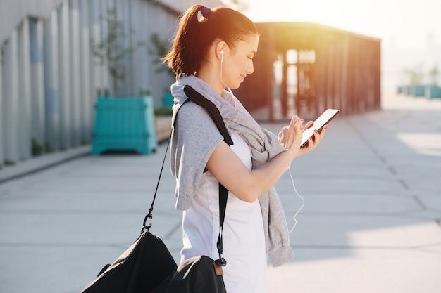 Vue latérale d'une femme athlétique en tenue sportive regardant son smartphone
