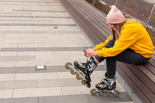 Vue latérale d'une femme attachant des cordes sur des patins à roues alignées