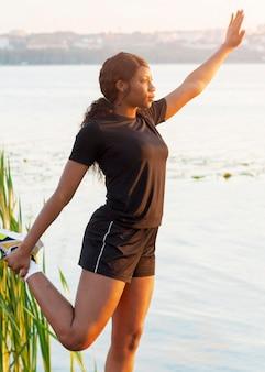 Vue latérale de la femme au bord du lac qui s'étend